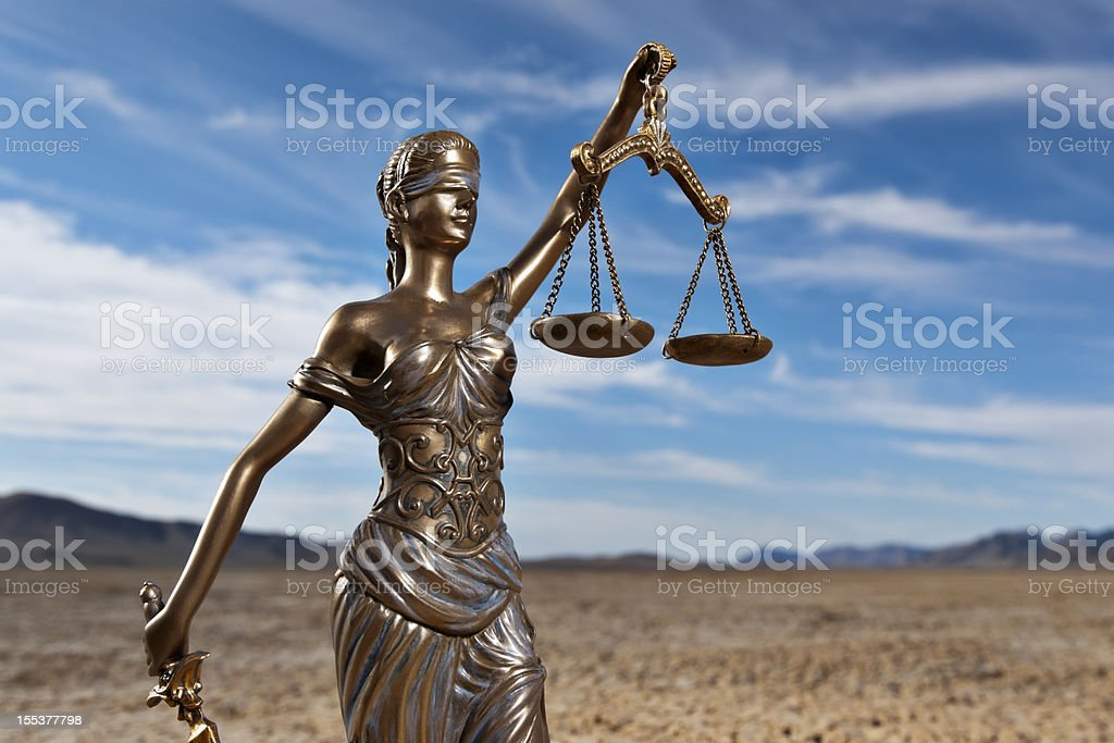 Bronze statue of Themis in dry lake bed royalty-free stock photo