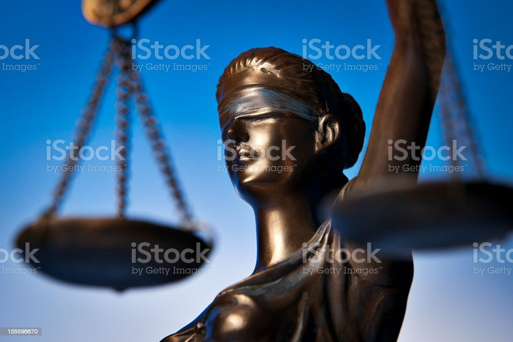 A bronze statue of Themis with a scale in front stock photo