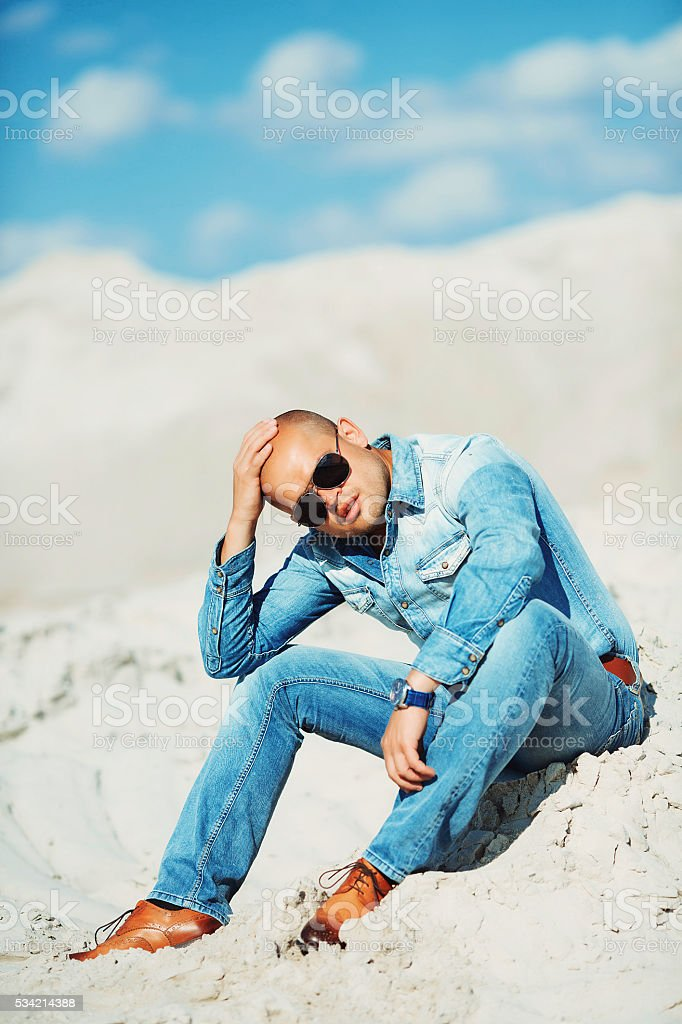 bronzed man sitting on the sand, holding his head royalty-free stock photo