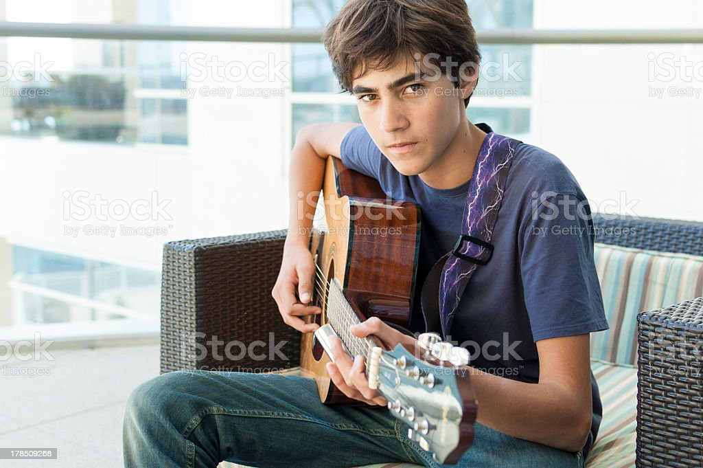 Brooding cute teenage boy playing Acoustic Guitar stock photo