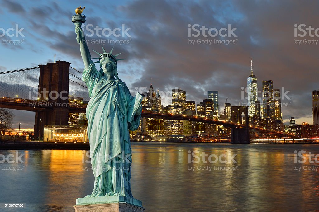 Brooklyn Bridge at night and Statue of Liberty. stock photo