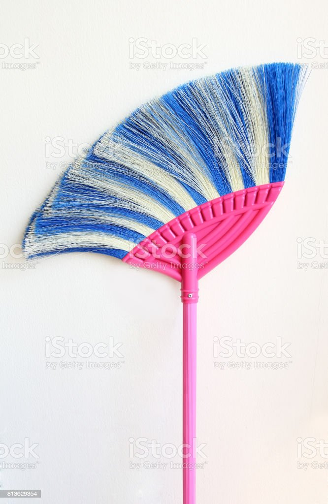 Broom placed on the white wall. stock photo
