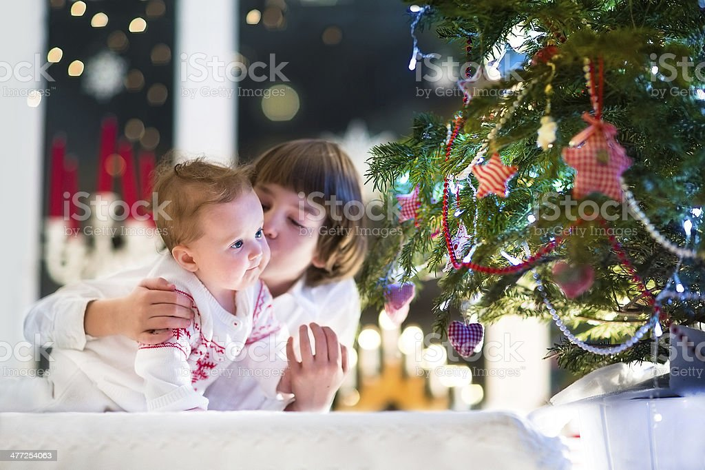 Brother and his baby sister playing together at Christmas tree royalty-free stock photo