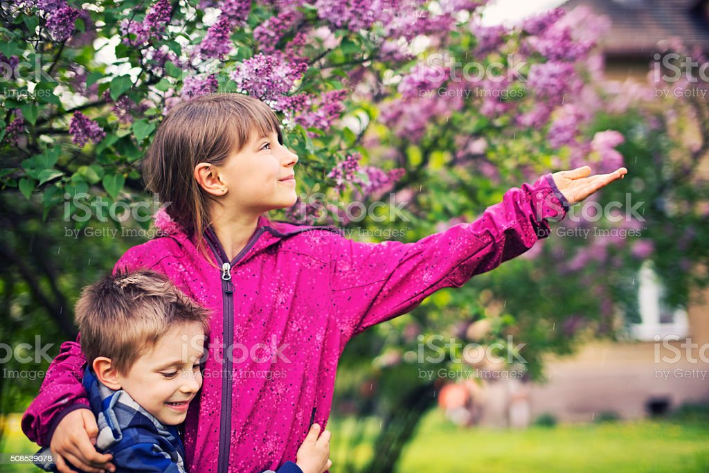 Brother and sister and spring rain stock photo