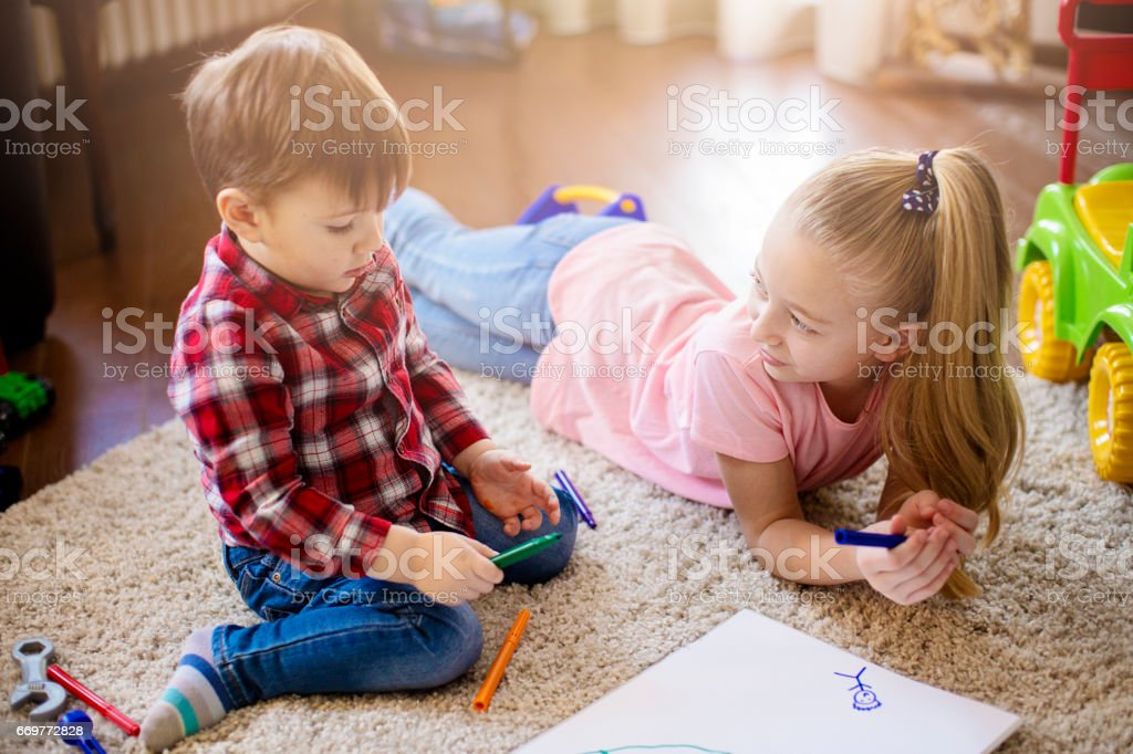 Brother and sister at the floor painting together stock photo