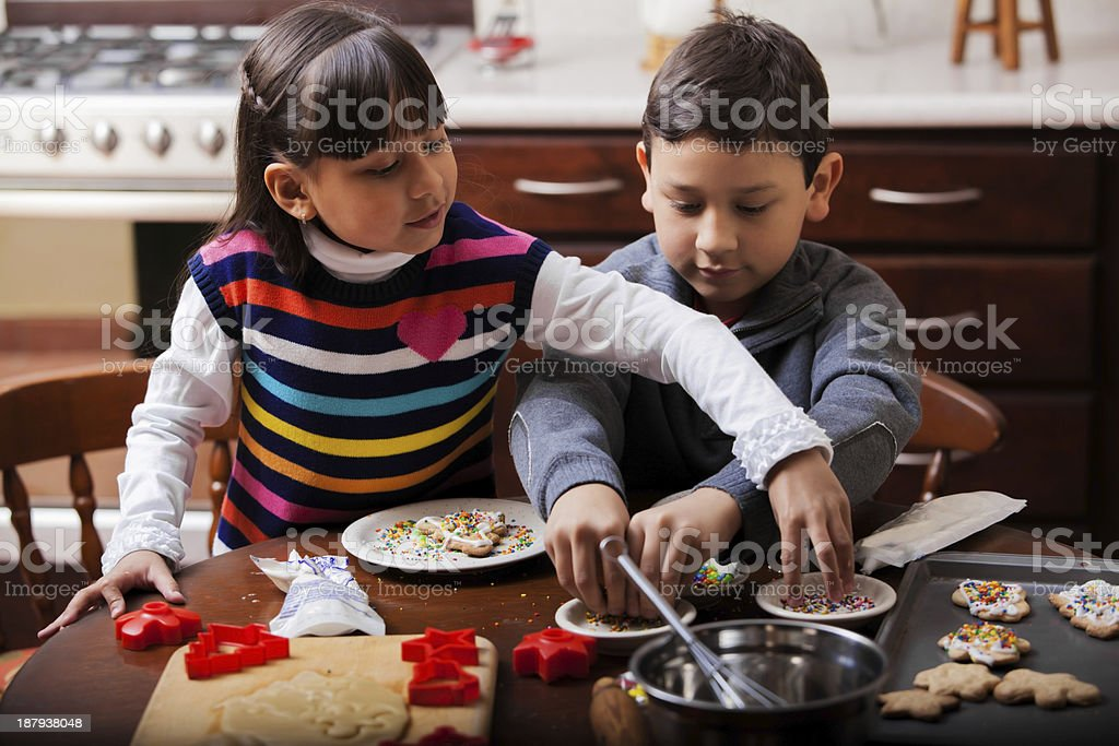 Brother and sister baking cookies stock photo