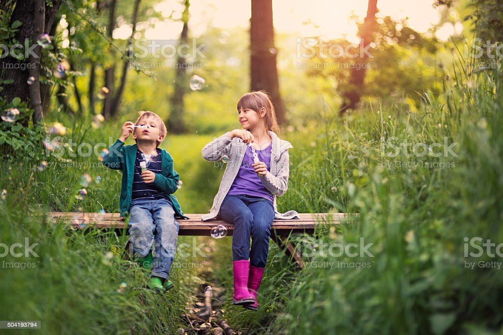 Brother and sister blowing  bubbles stock photo