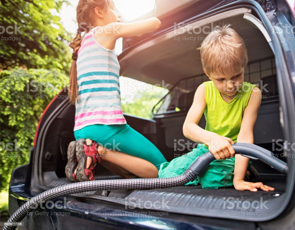 Brother and sister cleaning family car interior stock photo