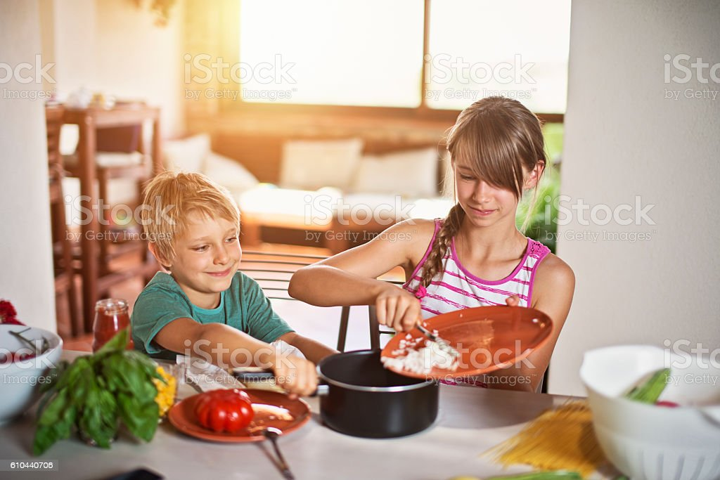 Brother and sister cookies spaghetti for dinner. stock photo