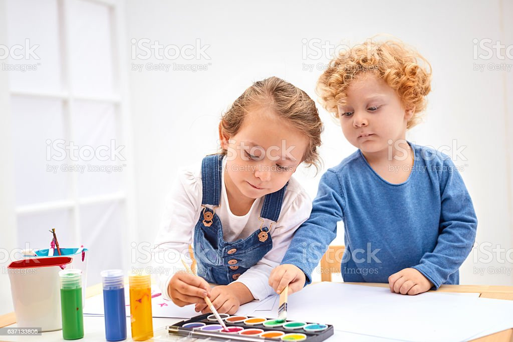 Brother and sister doing watercolor painting stock photo