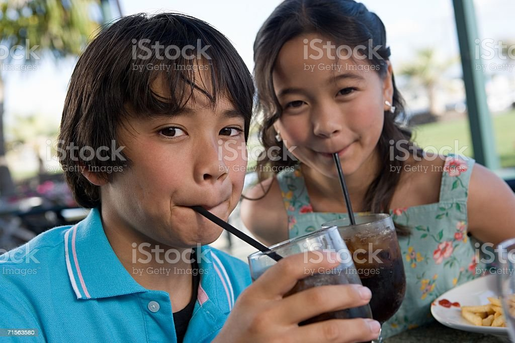 Brother and sister drinking cola stock photo