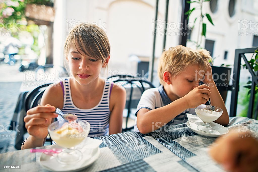 Brother and sister eating ice cream at cafe in Rome stock photo