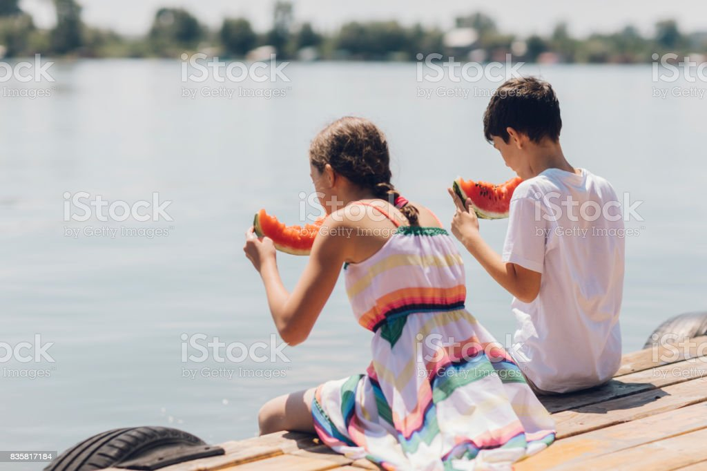 Brother and sister eating watermelon stock photo