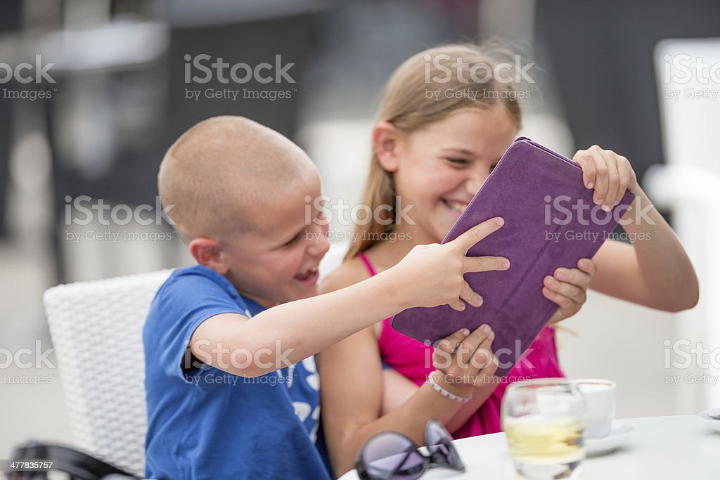 Brother and sister fighting for the tablet royalty-free stock photo