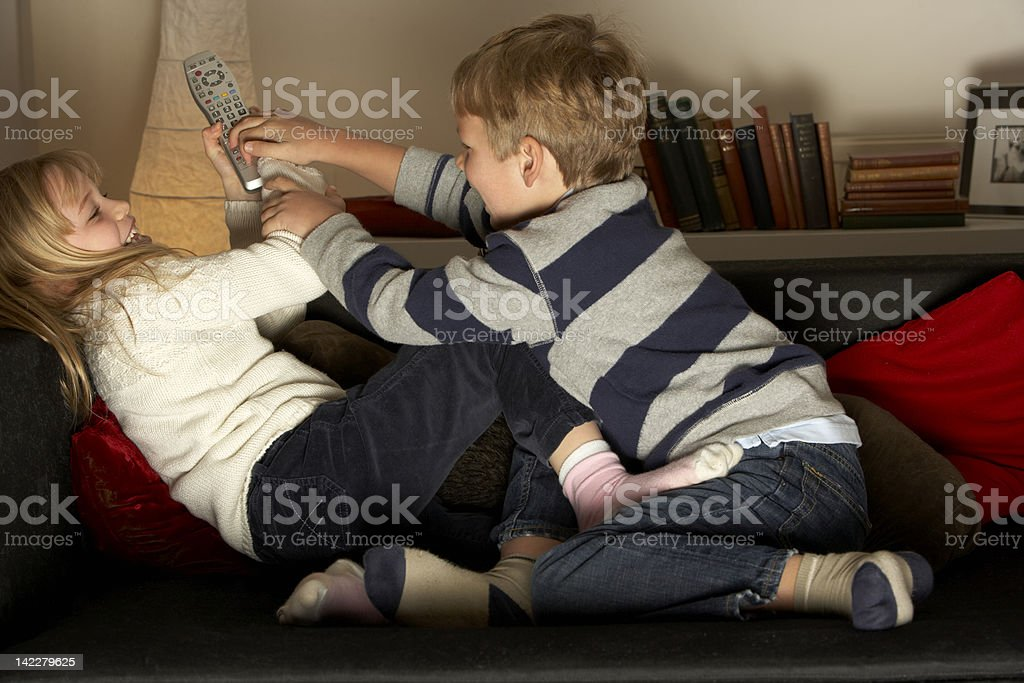 Brother And Sister Fighting Over Remote Control royalty-free stock photo