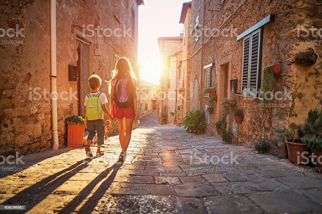 Brother and sister going to school in little town street. stock photo