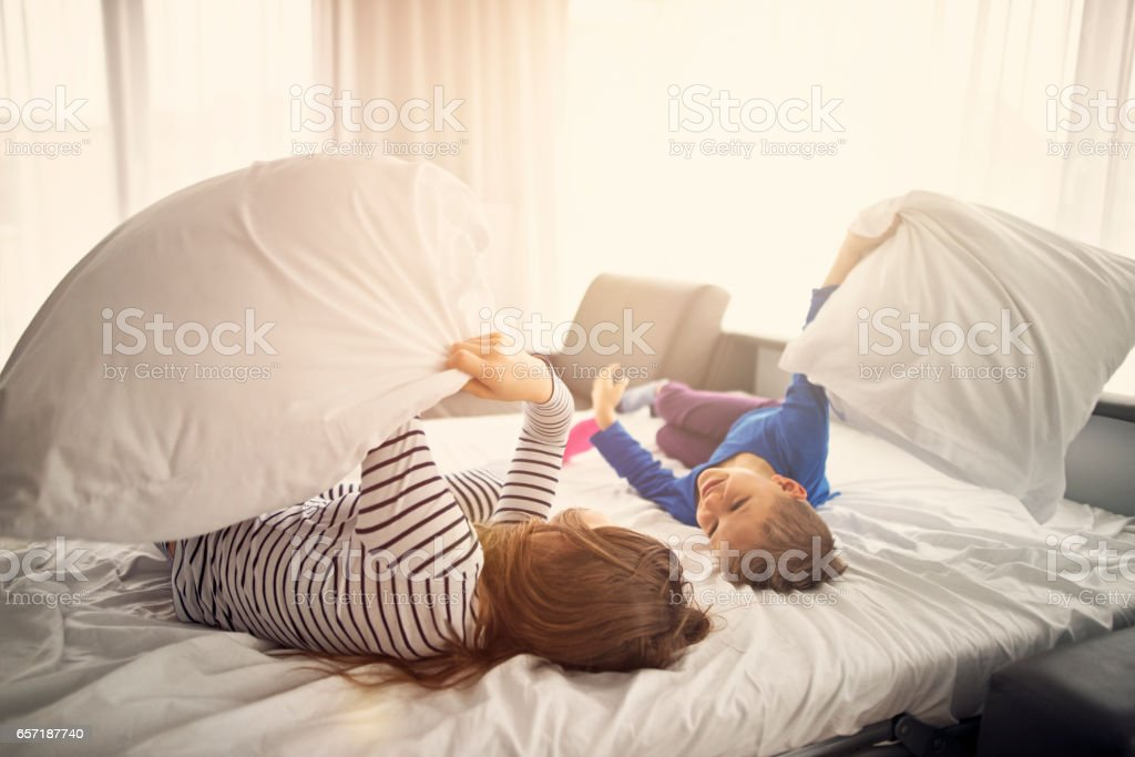 Brother and sister having a pillow fight on sunny morning stock photo