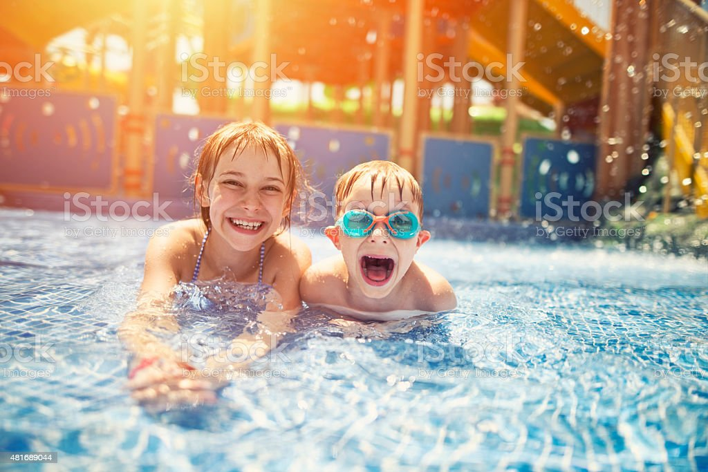 Brother and sister having fun in water park stock photo