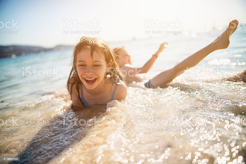 Brother and sister having fun in waves stock photo