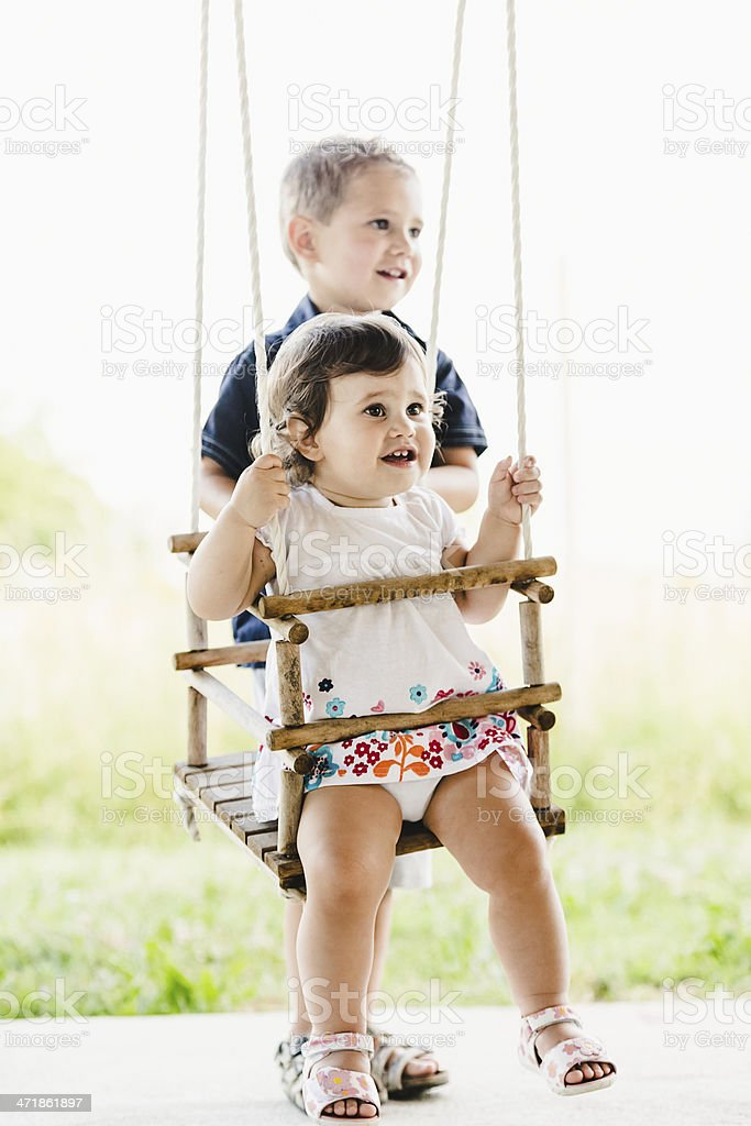 Brother and sister  having fun on a swing royalty-free stock photo