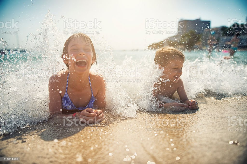 Brother and sister having fun splashed in sea stock photo