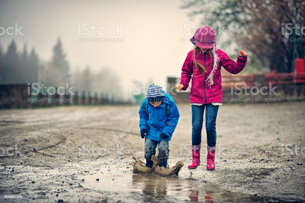 Brother and sister hikers playing in a early spring puddle stock photo