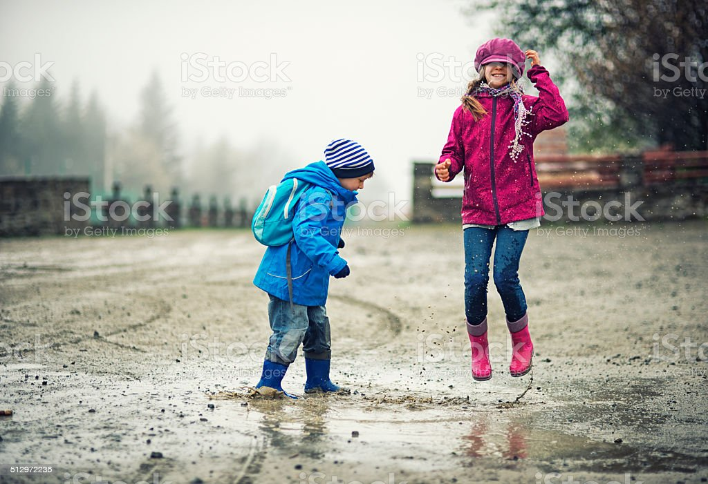 Brother and sister hikers playing in a puddle stock photo