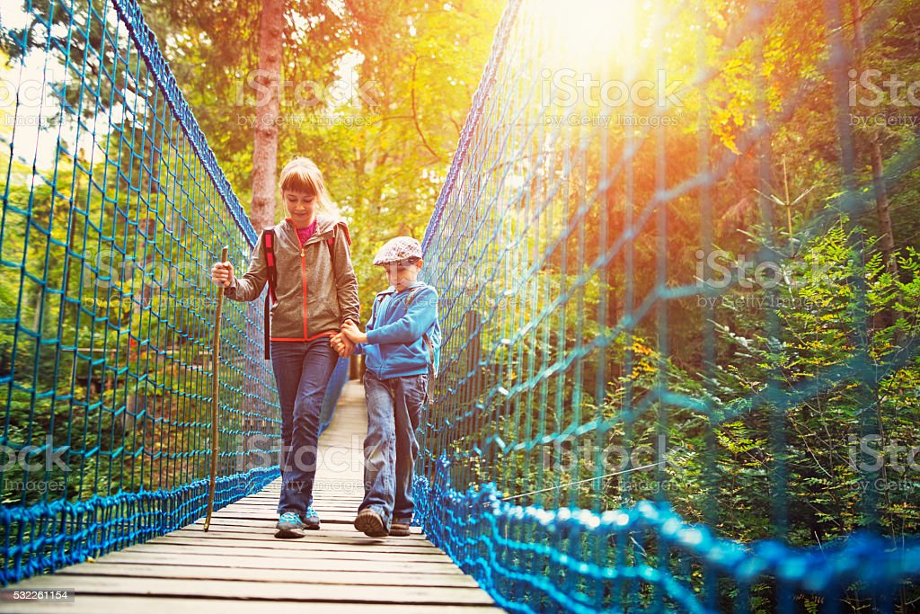 Brother and sister hikers walking on suspension bridge in forest stock photo