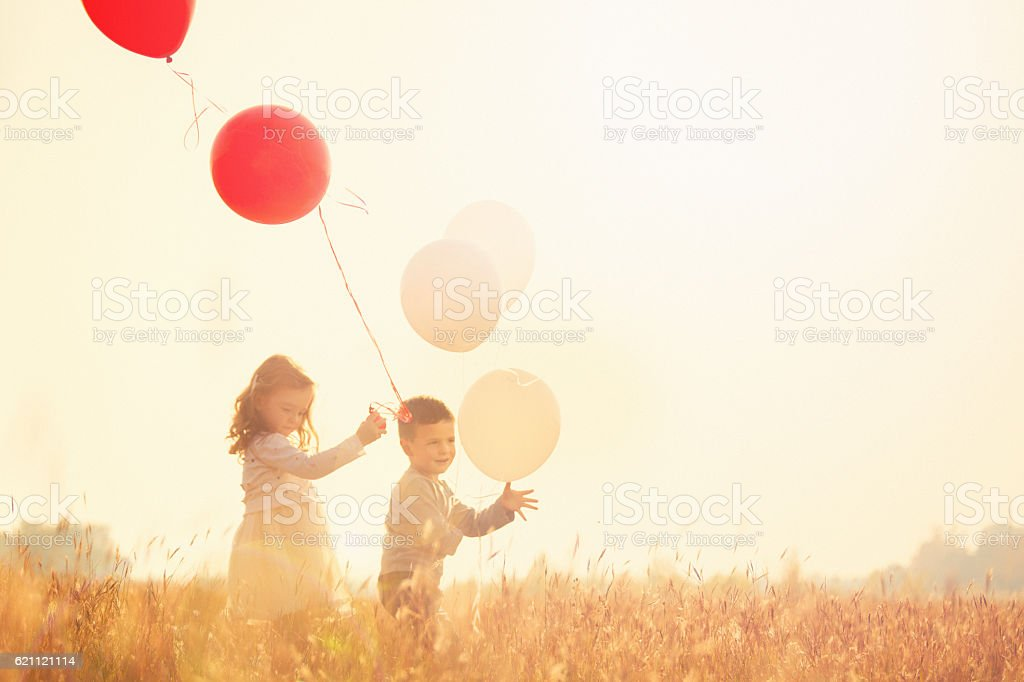 Brother and sister holding balloons and running stock photo