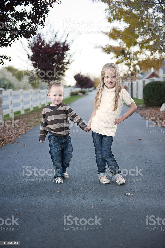 Brother and sister holding hands stock photo
