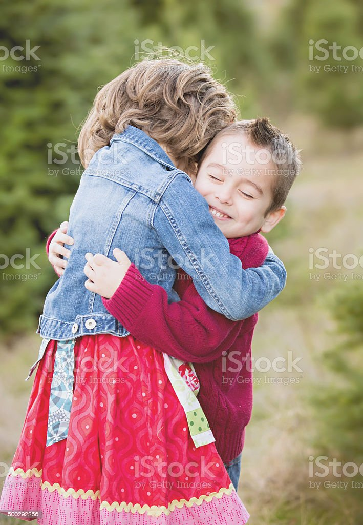 Brother and Sister hugging in Christmas Tree Farm . stock photo