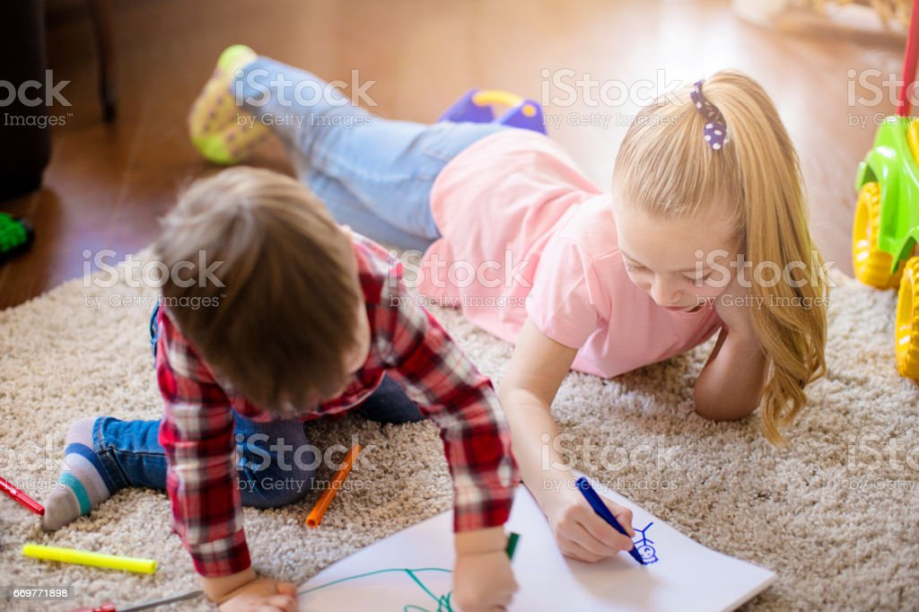 Brother and sister laying at the floor and painting together stock photo