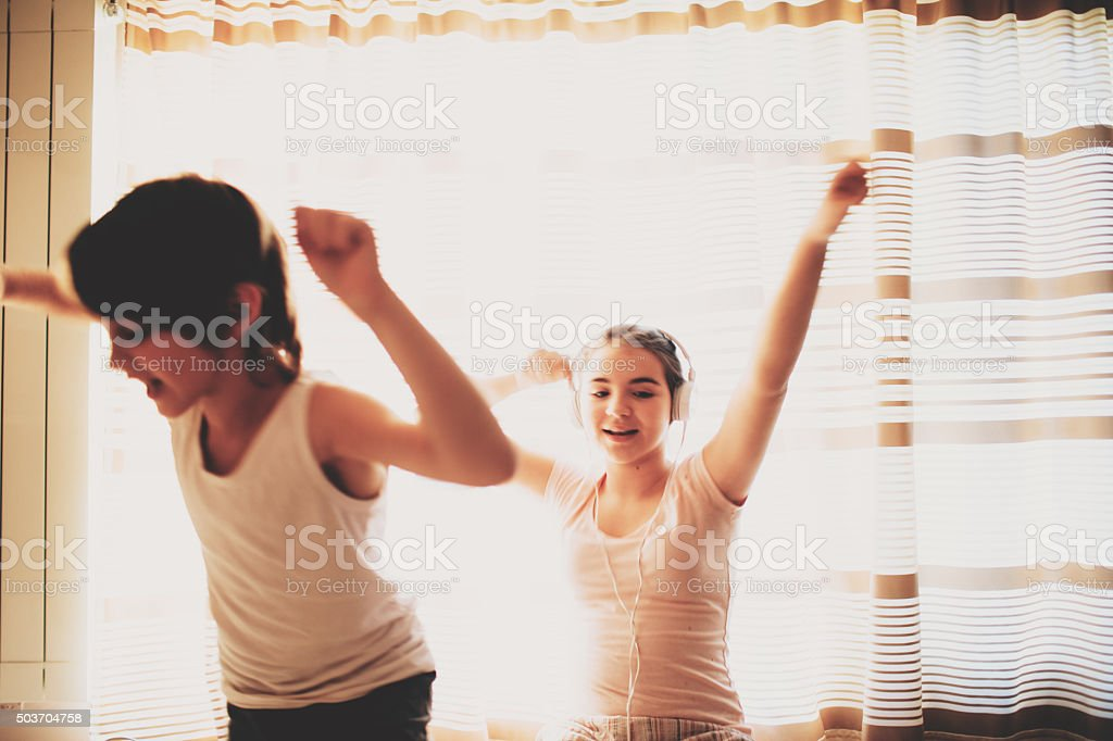 Brother and sister listening to music stock photo