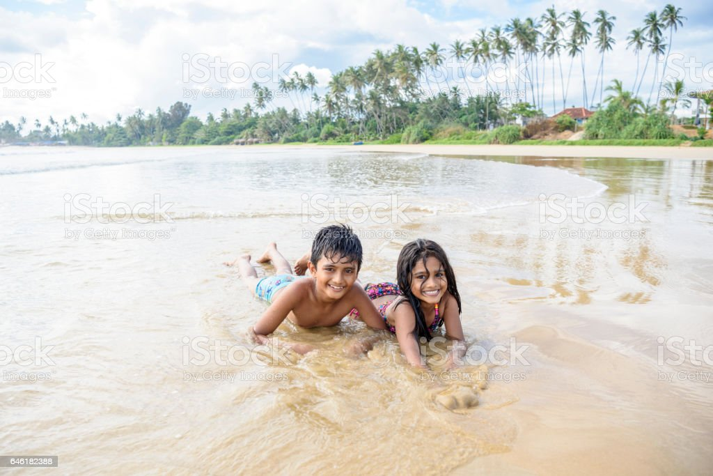 Brother and sister lying on sandy beach in sea stock photo