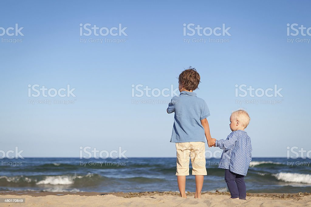 Brother and sister on walk near sea stock photo