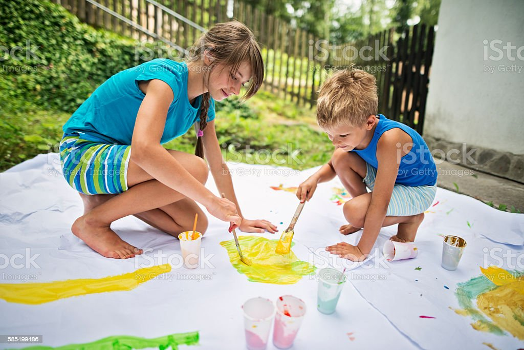 Brother and sister painting outdoors stock photo