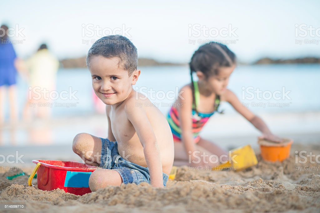 Brother and Sister Placing on a Sandy Beach stock photo