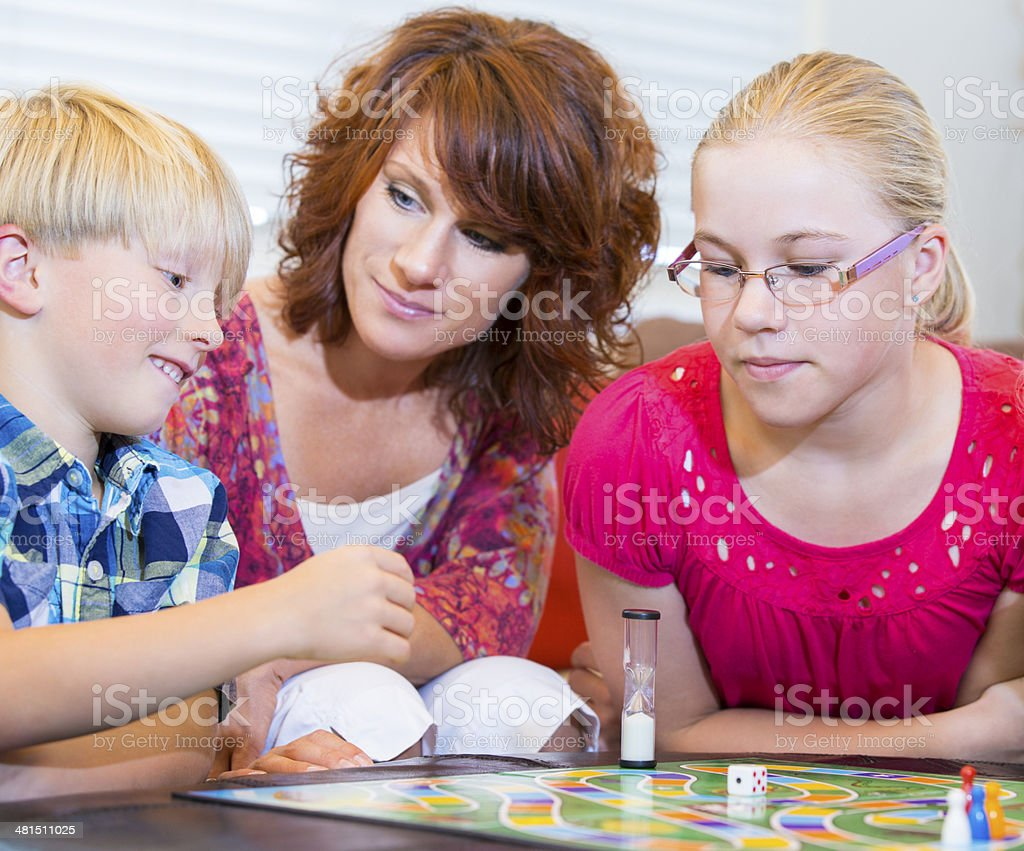 Brother and sister playing board games with their mom stock photo