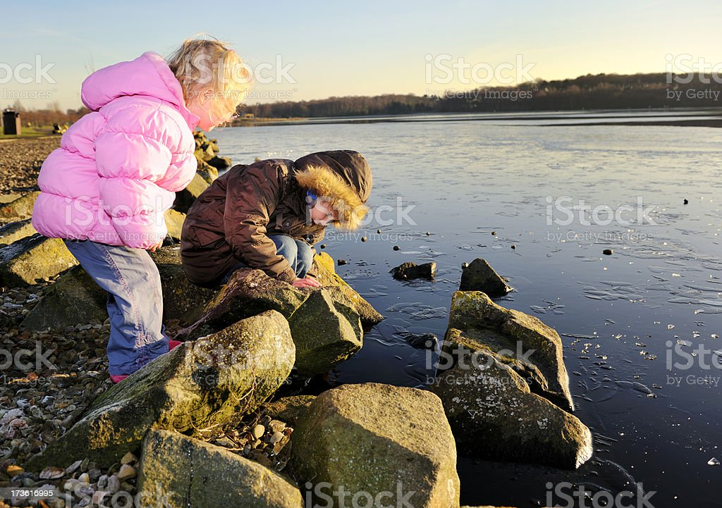 brother and sister playing by lakeside royalty-free stock photo