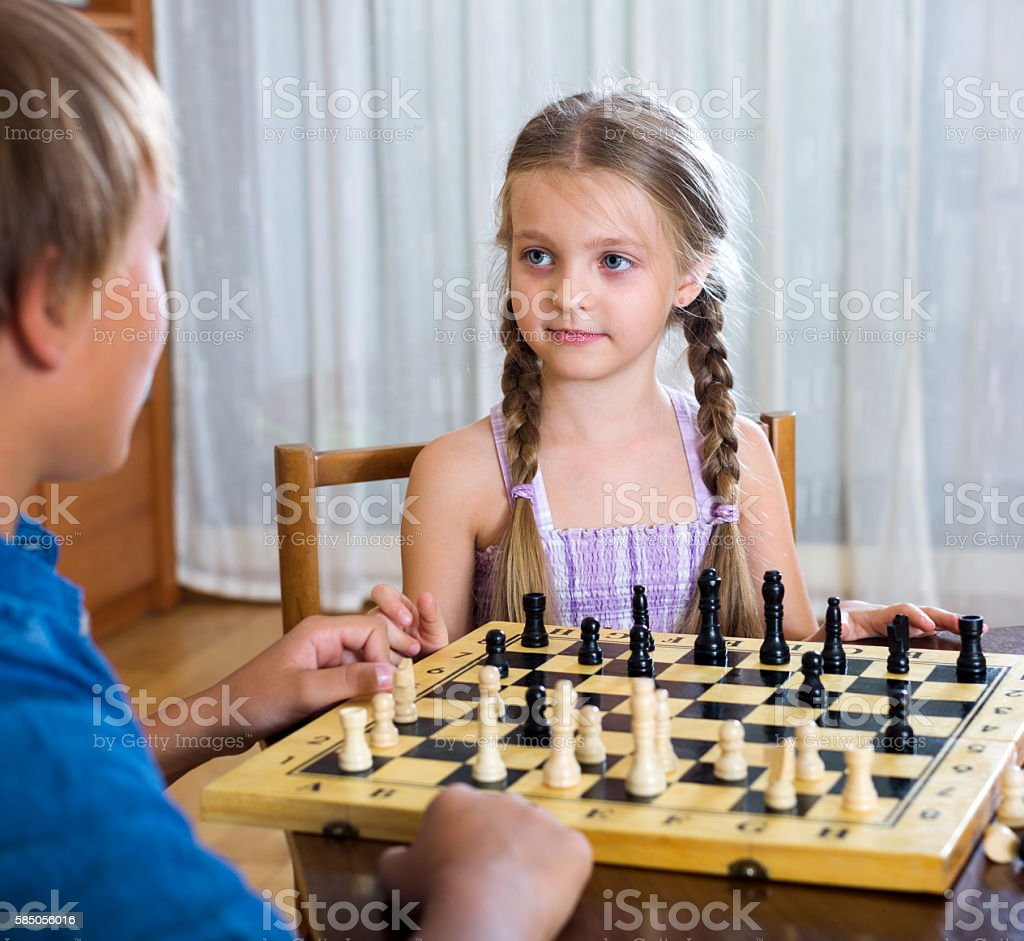 Brother and sister playing chess stock photo