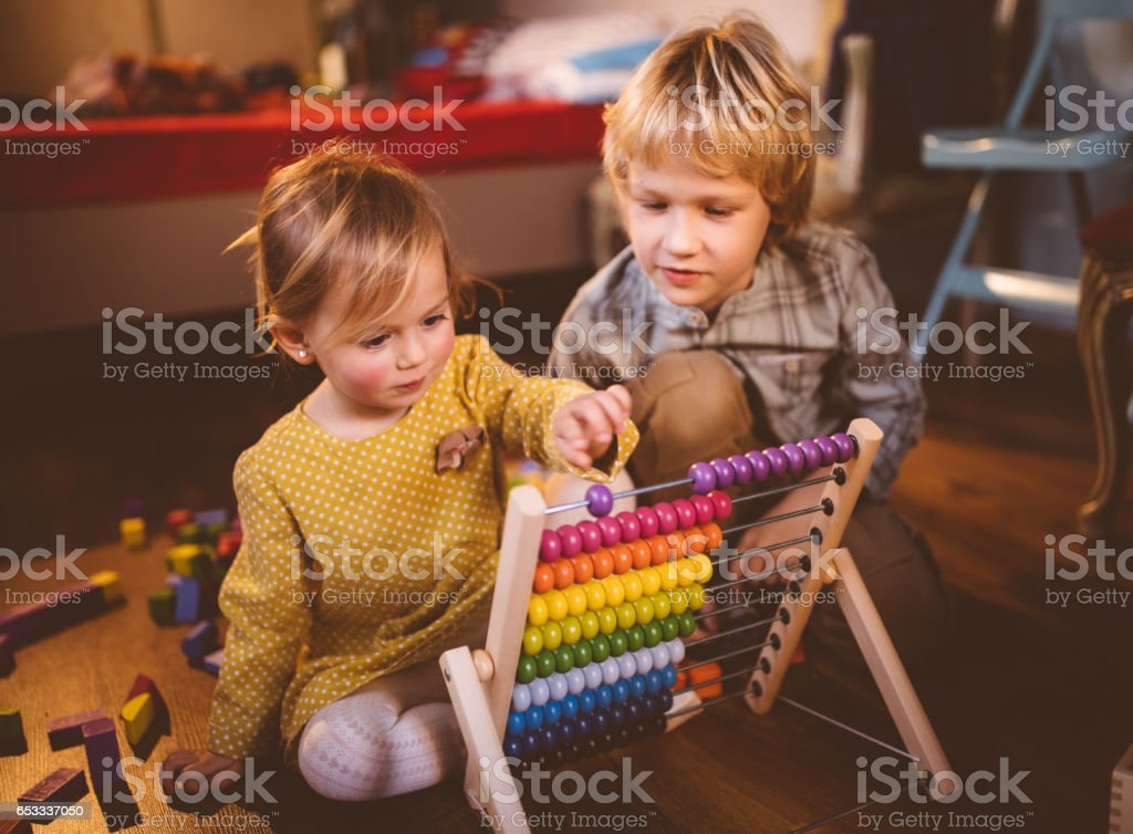 Brother and sister playing with abacus in their bedroom stock photo