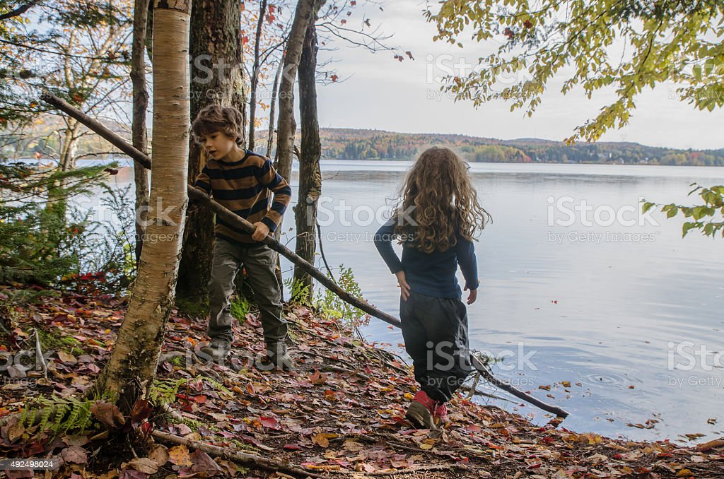 Brother and sister playing with branch on shore of lake stock photo