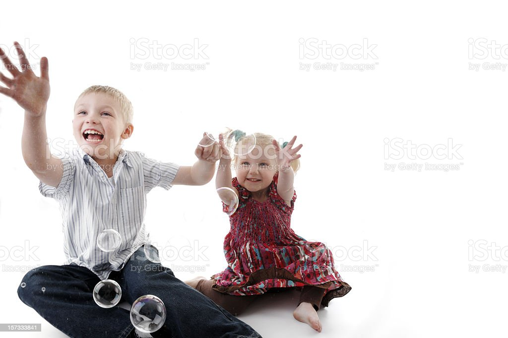 brother and sister playing with bubbles royalty-free stock photo