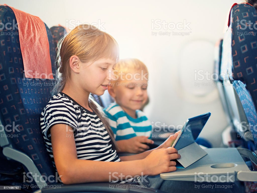 Brother and sister playing with tablet in plane stock photo