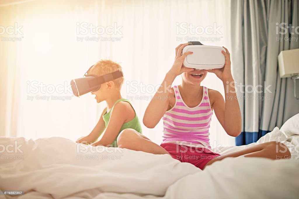 Brother and sister playing with virtual reality headsets stock photo