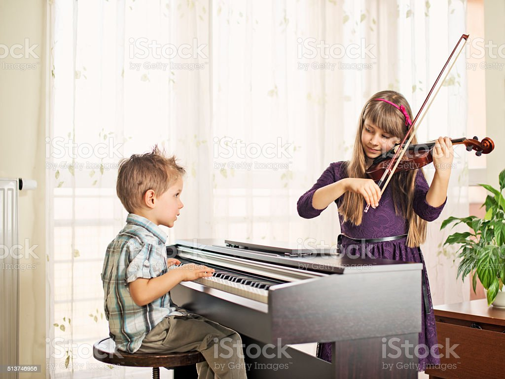 Brother and sister practicing piano and violin stock photo