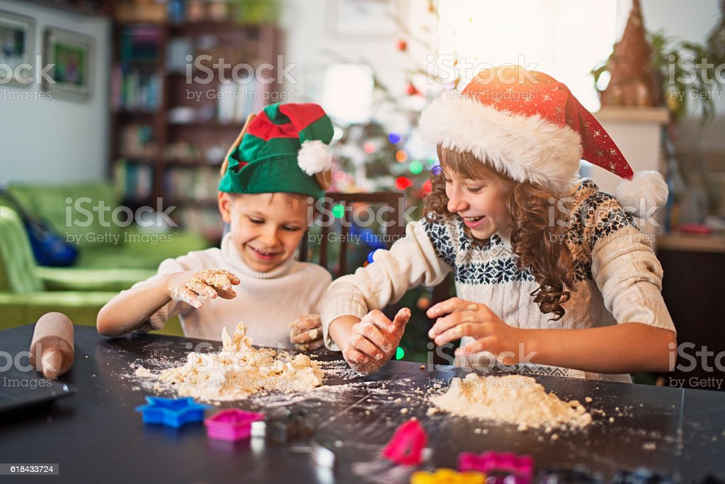Brother and sister preparing christmas cookies stock photo