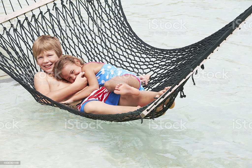 Brother And Sister Relaxing In Beach Hammock royalty-free stock photo