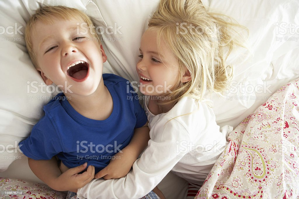 Brother And Sister Relaxing Together In Bed stock photo