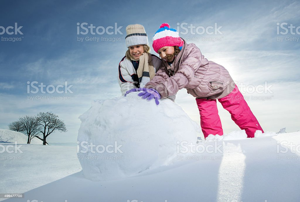 Brother and sister rolling snowball to make snowman. stock photo